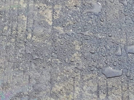Water beading on a sealed concrete surface.