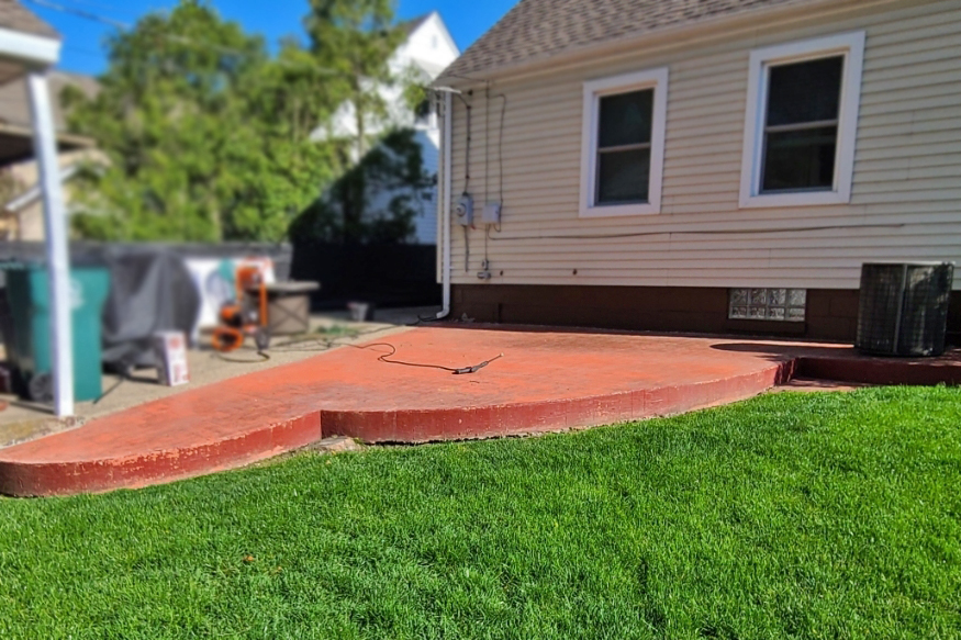 Red stamped concrete patio before applying Antiquing stain