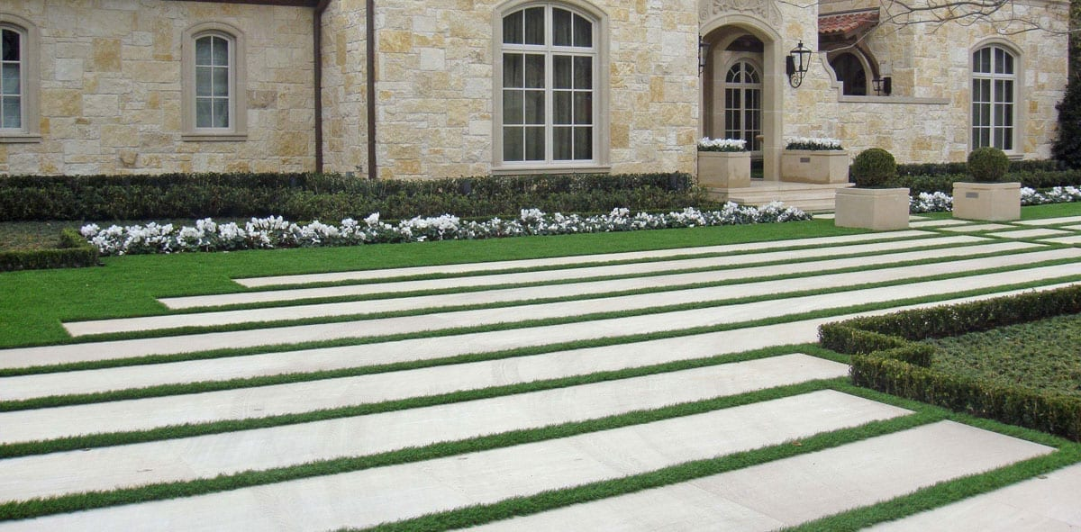 Patio paver bands line a driveway in front of a mansion.
