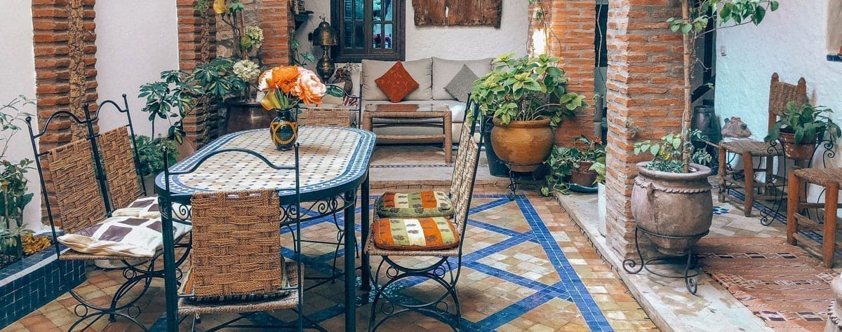 A beautiful patio is colored with bright blue concrete pavers using outdoor concrete stain.