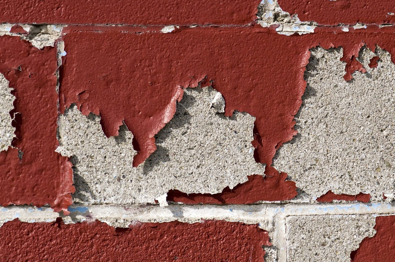 Red paint chips from an underlying concrete wall.