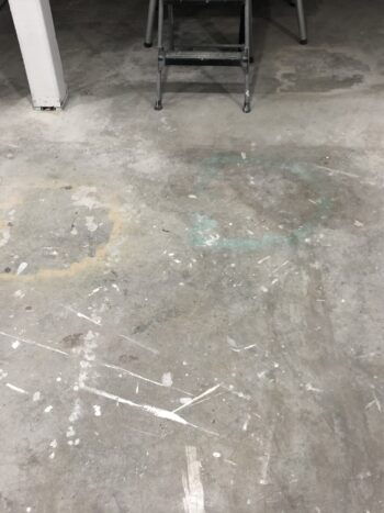 Basement floor with old stains, spray paint and overspray on it